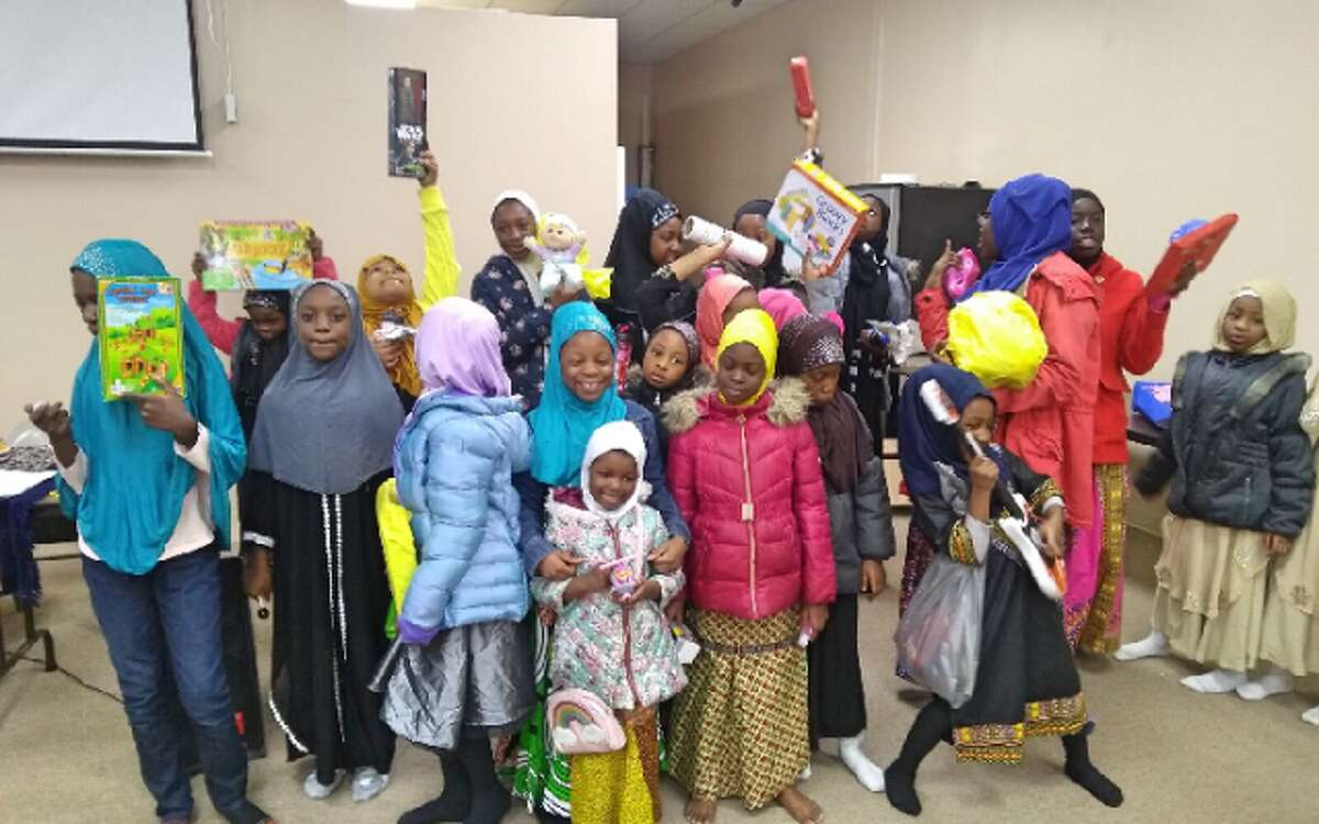 Children at the New Haven-based Baquis Fellowship receive their toys. - Submitted