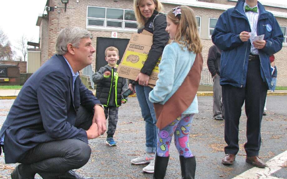 Republican gubernatorial candidate Bob Stefanowski greets Brownie Scout Lyla Delrossi, 7, her brother Luke, 5, and mother Erin at Middlebrook school. — Donald Eng photo
