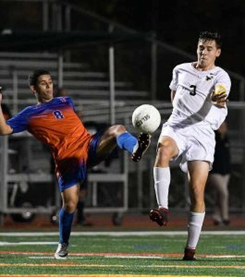 Trumbull's Bryant Recker battles Danbury's' Erick Costa in the FCIAC final. — David G. Whitham photo