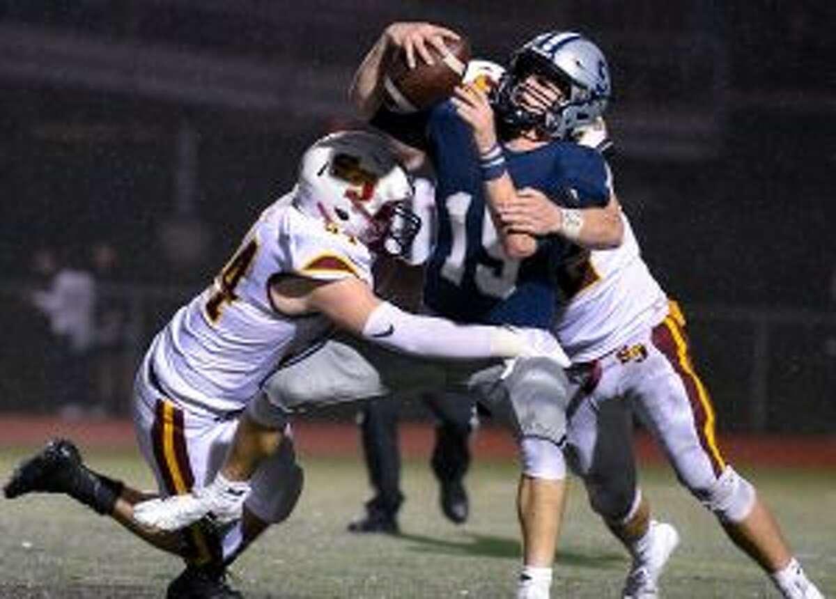 Alex Pagliarini and Cole daSilva combine to bring down Staples' quarterback Jake Thaw.