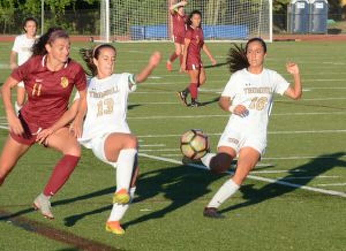 Trumbull's Jessica Esposito and Elizabeth Foley look to fend off Maddie Fried.