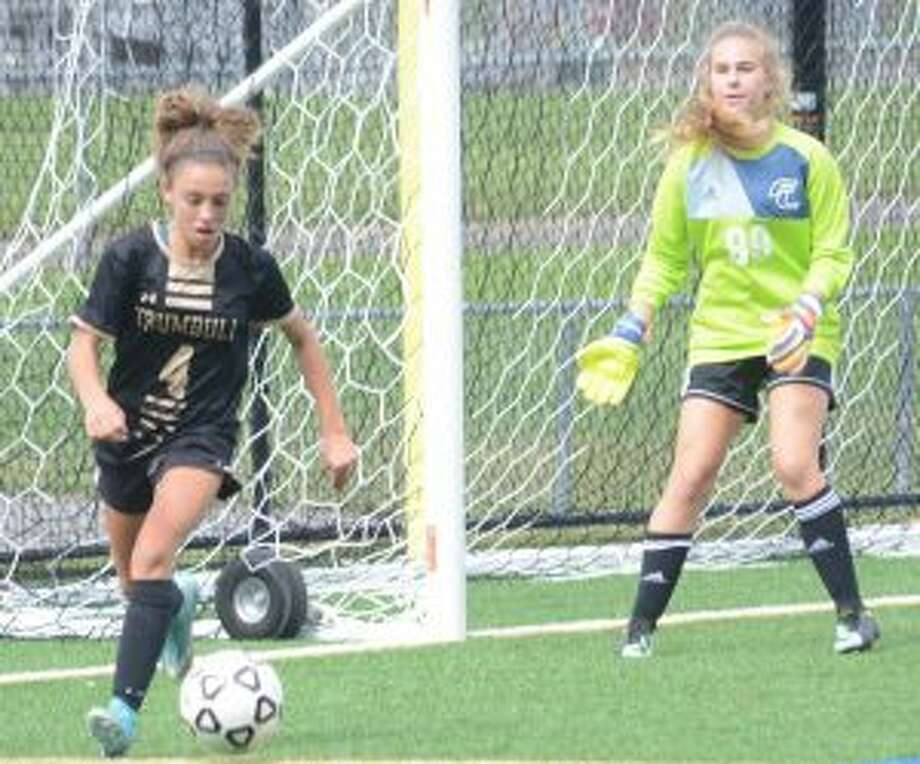 Mia DiBello looks to control the ball, as Ludlowe keeper Julia Pida waits. — Andy Hutchison photo