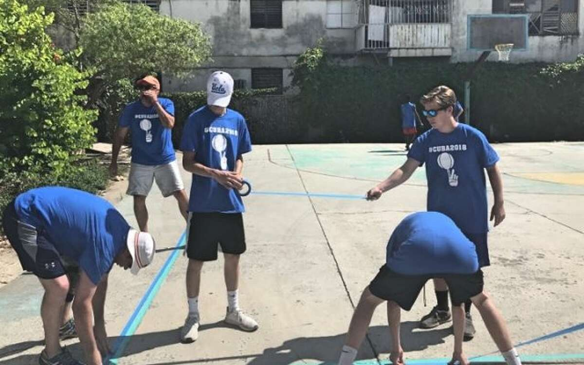 Trumbull sophomore Lance Walsh (white hat) helps paint a basketball court in Cuba.