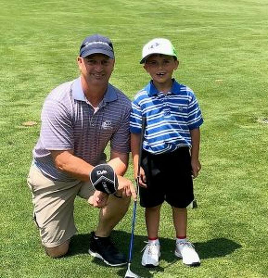 Jack Doran and his caddie-dad Matt get together after his hole in one.