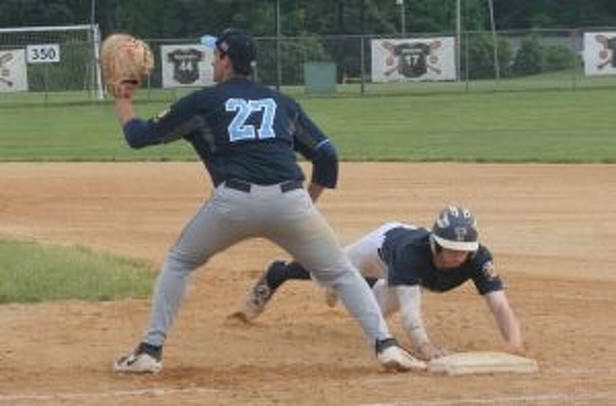 Trumbull's Jack Lynch, who had four hits, dives back into first base safely.
