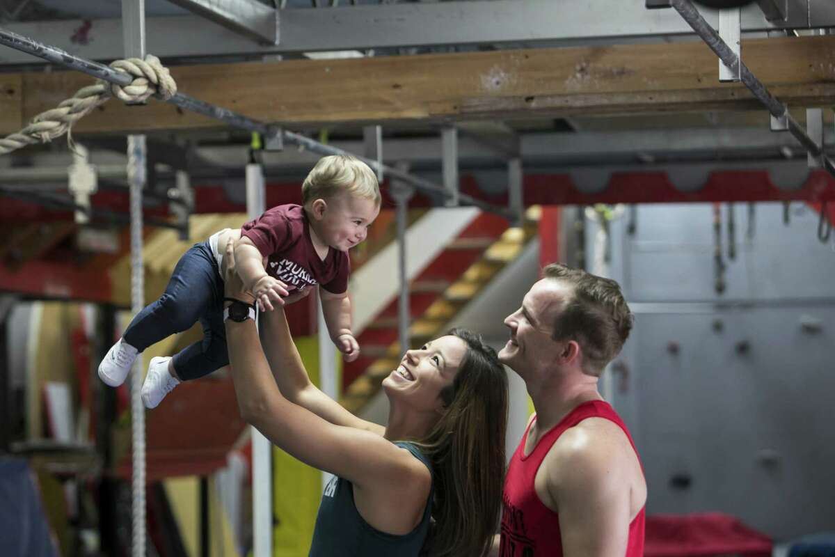 Lauren and Mike Murray with their 10-month-old daughter Emma at Iron Sports Gym in Cypress.