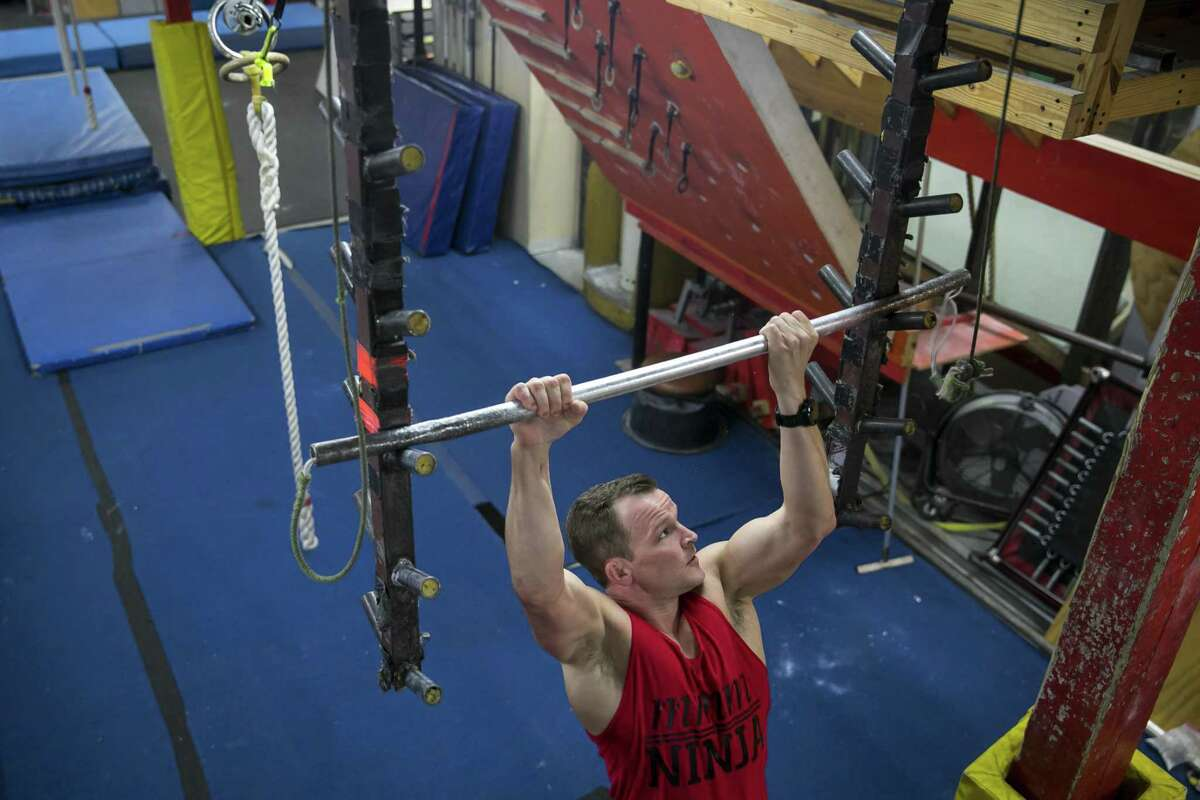 Mike Murray completes an 'American Ninja Warrior' obstacle at Iron Sports Gym in Cypress.