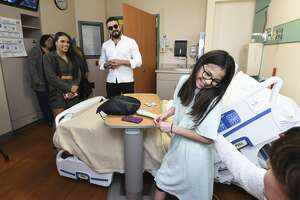 WWE wrestlers Zelina and Andrade surprise Larissa Garcia on Monday, Jun 3, 2019, as the performers visit children at the Laredo Medical Center's pediatrics ward.