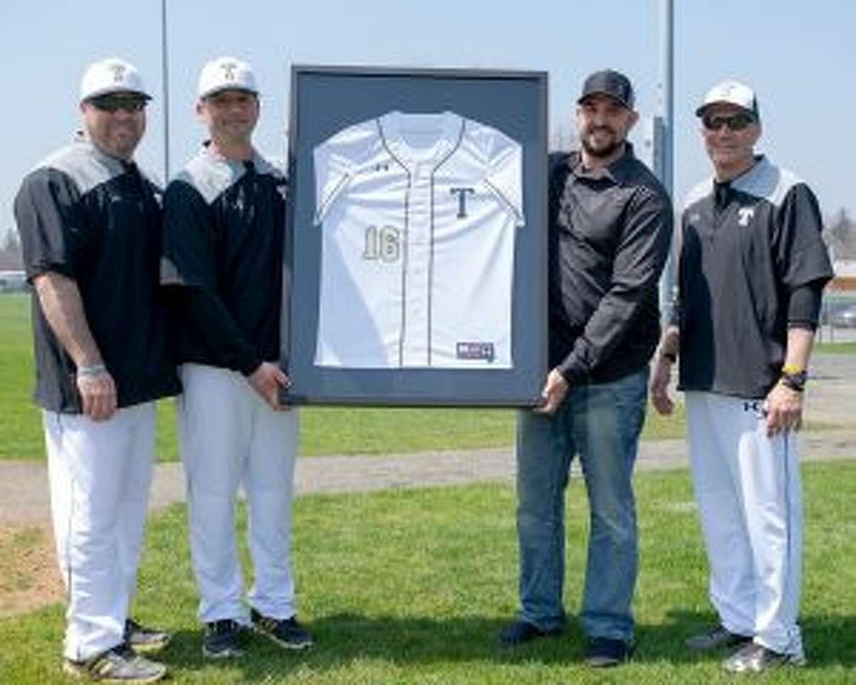 Tim Tvardzik, a pitcher on the 1998 team, Trumbull head coach Phil Pacelli, Jamie D'Antona, who went on to play for the Arizona Diamondbacks, and Buddy Bray, an assistant coach on Trumbull's last state title-winning baseball team, stand with the framed jersey presented to D'Antona. - David G. Whitham photo