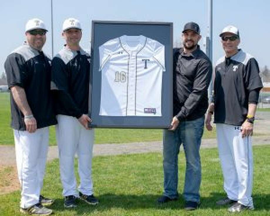 Tim Tvardzik, a pitcher on the 1998 team, Trumbull head coach Phil Pacelli, Jamie D'Antona, who went on to play for the Arizona Diamondbacks, and Buddy Bray, an assistant coach on Trumbull's last state title-winning baseball team, stand with the framed jersey presented to D'Antona. — David G. Whitham photo