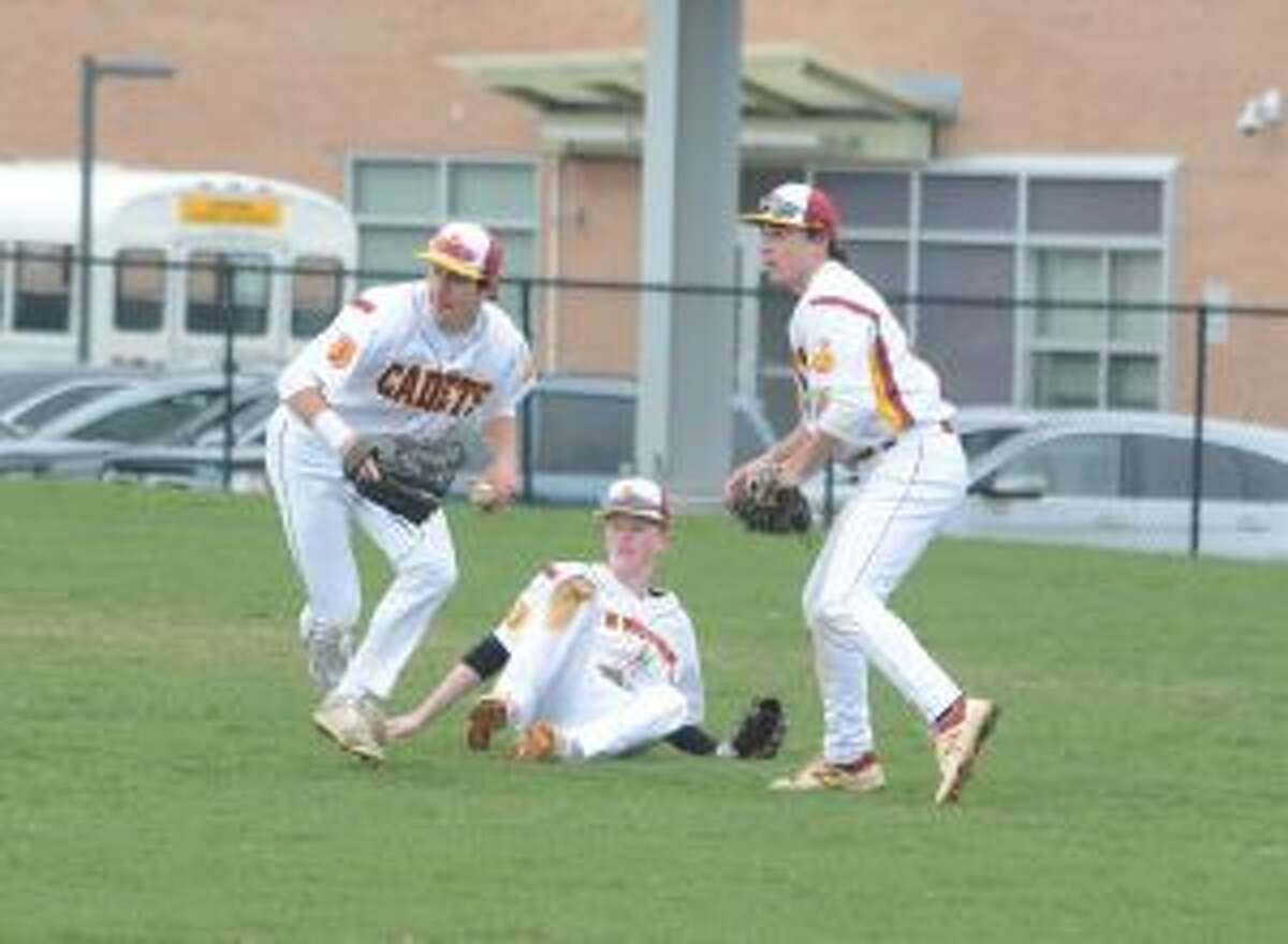 Right fielder Stephen Paolini throws the ball in as second baseman Owen Horne (on the ground) and center fielder Jake DeLeo look on.