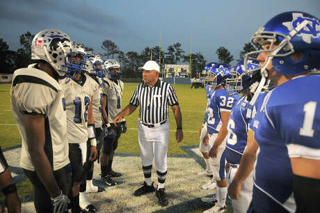 Referee Mike Atkinson, center, of Spring, briefs the New Caney and Chavez captins during their ceremonial pre-game coin toss.