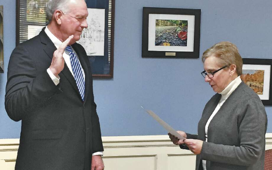 New Police Commissioner Ray Baldwin is sworn into the commission by First Selectman Vicki Tesoro.