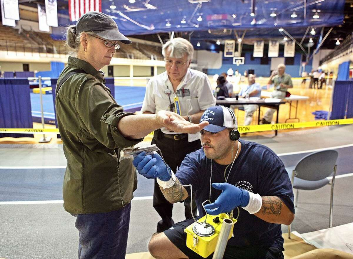 """New Haven Firefighter Roberto Lugo, right, uses a radiation detection device (Geiger Counter) to sweep """"Victim"""" Sandy Rhodes as Controller John Waggoner (With the DEP Radiation Division) watches during a mock radiation drill at SCSU's Moore Fieldhouse. Photo-Peter Casolino"""