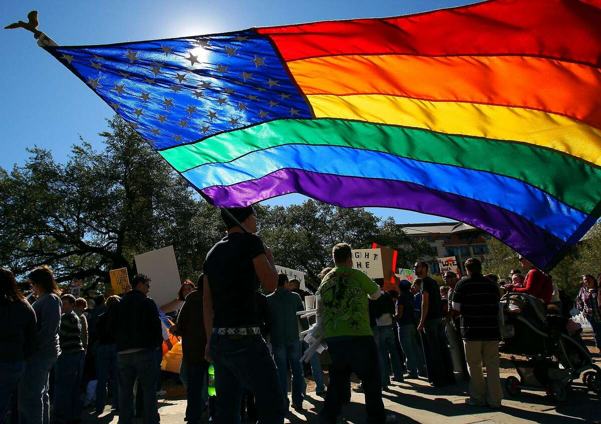 FOR METRO - Roger Woodard carries a combination American and Rainbow flag while attending the National Day of Protest against Proposition 8 rally, which banned gay marriage in California, Saturday Nov. 15, 2008 in Main Plaza. (PHOTO BY EDWARD A. ORNELAS/eornelas@express-news.net)