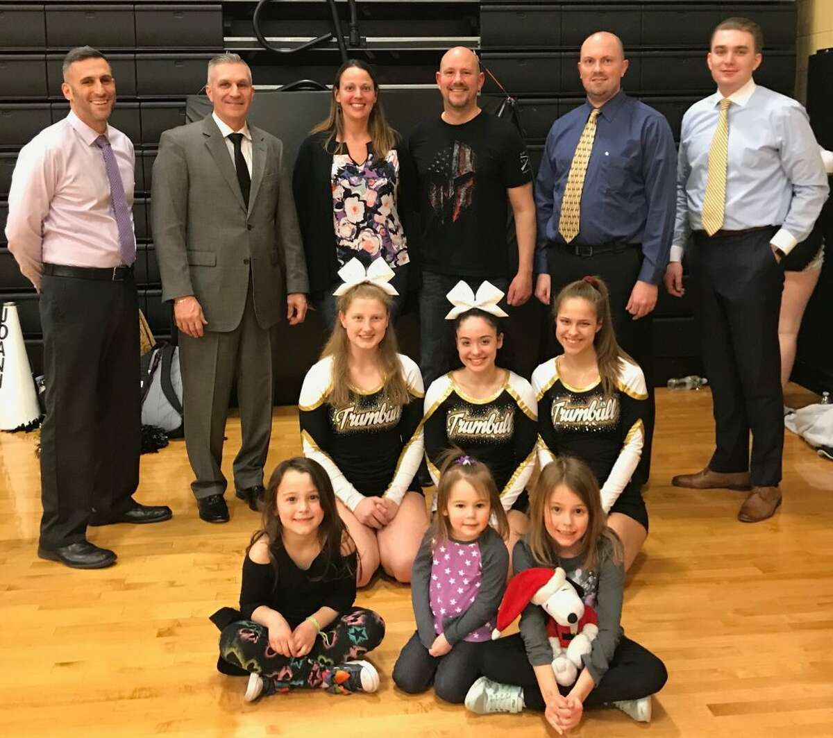 Kief Doyle was honored by the Trumbull High boys basketball program for his military service to our country. Pictured (front row) are daughters Brooklyn Doyle, Cassidy Doyle and Addison Doyle; (second row) THS cheerleaders Katelyn Miller, Joanna Vizcarrondo and Ashley Deal; (third row) Trumbull assistant coach Matt Landin, head coach Buddy Bray, wife Rachel Doyle, Keif Doyle, assistant coach Bob Packer and assistant coach Cliff Bray.