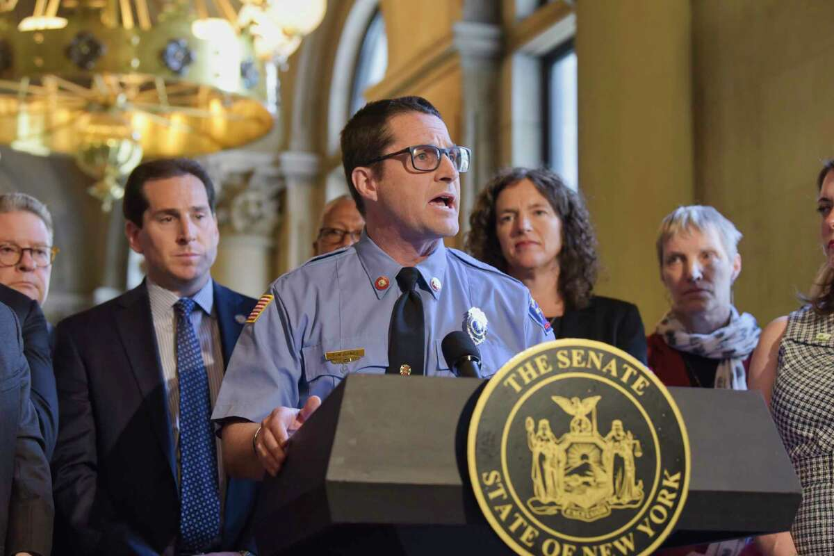 Tim Guinee, a volunteer firefighter, actor and member of the Climate Reality Project along with Senators, Assembly members and other supporters of climate legislation hold a press conference to discuss their push for legislation on Tuesday, June 4, 2019, in Albany, N.Y. (Paul Buckowski/Times Union)