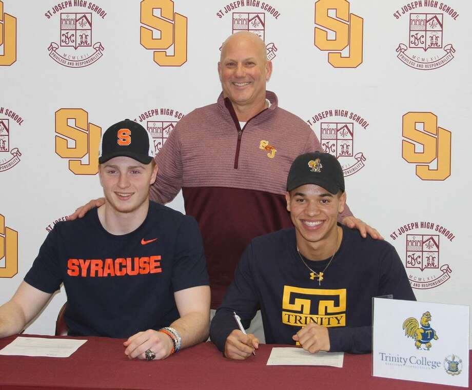 St. Joseph High football coach Joe Della Vecchia stands behind David Summers (Syracuse University) and Darren Warren (Trinity College) after they signed National Letters of Intent.Photo: St. Joseph High
