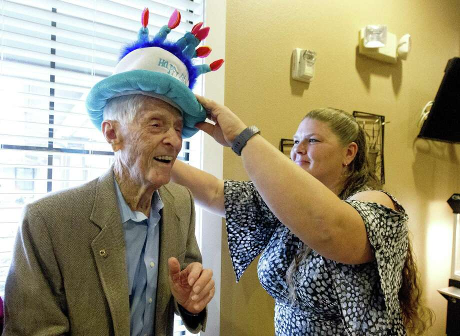 Katherine Appodaca puts a birthday hat on Morris Bateman during a party in celebration of his 103rd birthday at Heritage Oaks, Wednesday, Dec. 12, 2018, in Conroe. Photo: Jason Fochtman, Houston Chronicle / Staff Photographer / © 2018 Houston Chronicle