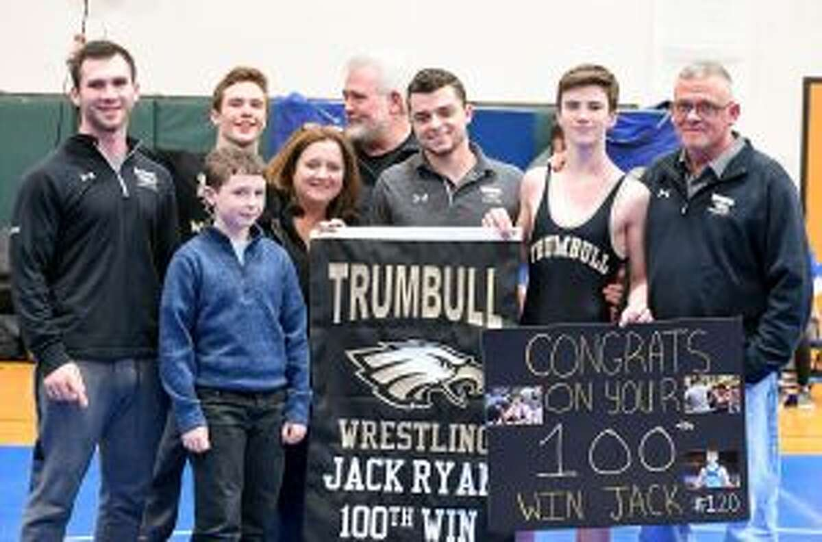 Jack Ryan won his 100th match versus Ludlowe. Pictured are brother's Joey, Matt and Shane, along with mom Geraldine, dad Joe and coaches Ben and Charlie Anderson. Missing from photo is sister Kelsey (cheerleading). - David G. Whitham photos