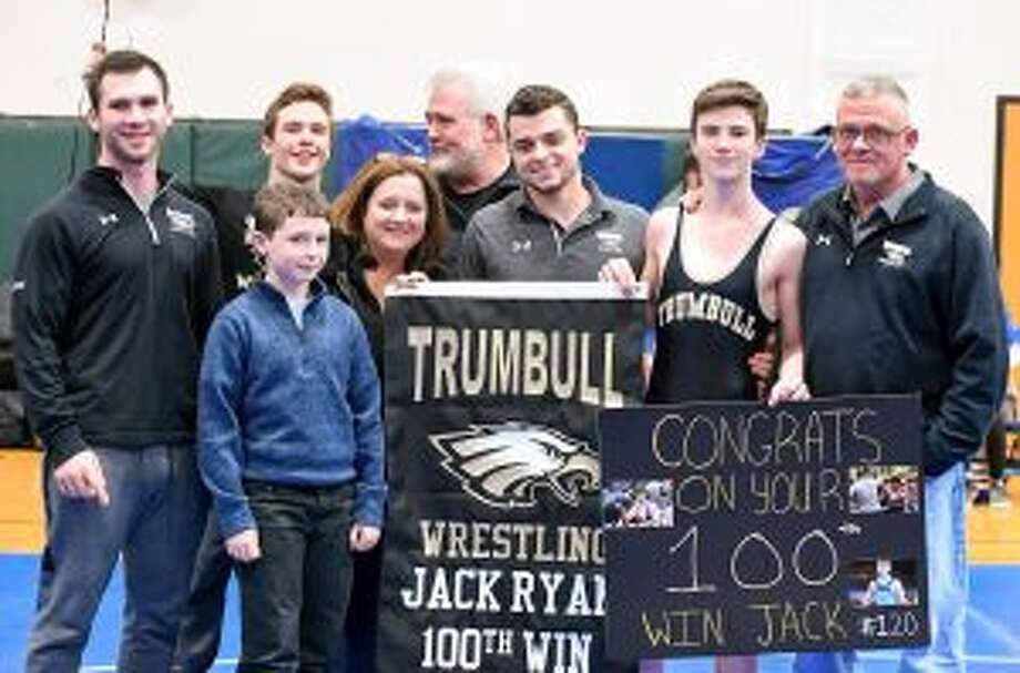 Jack Ryan won his 100th match versus Ludlowe. Pictured are brother's Joey, Matt and Shane, along with mom Geraldine, dad Joe and coaches Ben and Charlie Anderson. Missing from photo is sister Kelsey (cheerleading). — David G. Whitham photos