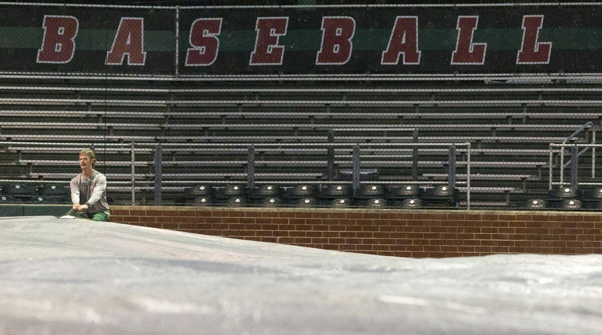 The Woodlands assistant coach John Hays helps tarp the infield of Scotland Yard after lightning interrupted Game 1 of Region II-6A bi-district high school baseball playoff series between The Woodlands and Aldine MacArthur, Thursday, May 2, 2019, in The Woodlands.