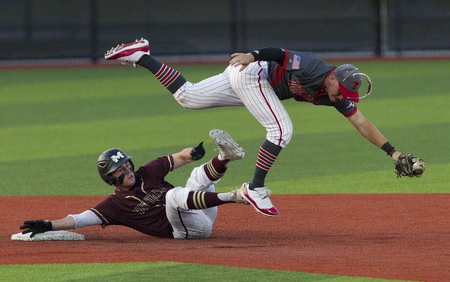 Tomball shortstop Kasen Handal (7) leaps over Zach Wall #8 of Magnolia West after tagging him out attempting to steal second in the second inning during Game 1 of a Region III-5A quarterfinal high school baseball series at Grand Oaks High School, Thursday, May 16, 2019, in Spring. Photo: Jason Fochtman/Staff Photographer
