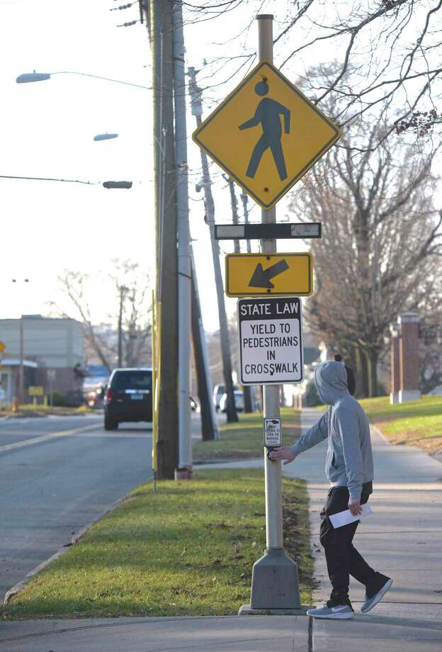 A pedestrian prepares to cross White Street in Danbury in December 2018. Photo: H John Voorhees III / Hearst Connecticut Media / The News-Times