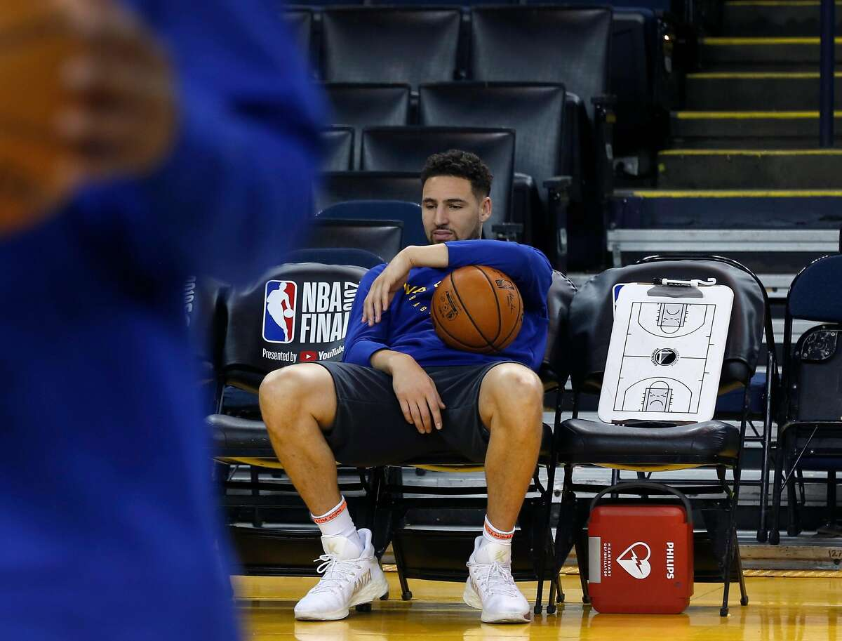 Klay Thompson sits on the bench during a Golden State Warriors practice at Oracle Arena in Oakland, Calif. on Tuesday, June 4, 2019 before tomorrow's Game 3 of the NBA Finals against the Toronto Raptors.