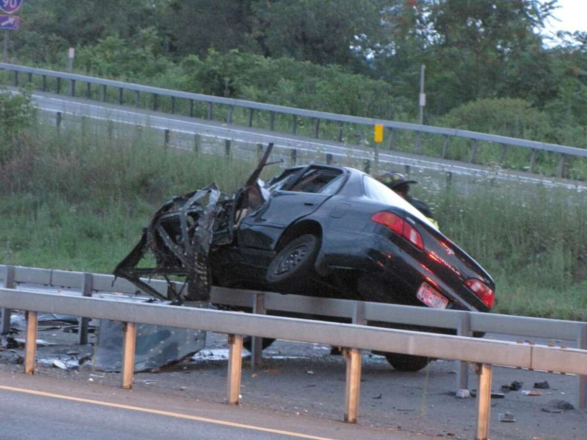 A car rests on a guardrail after an early morning collision on Interstate 787. The car was heading the wrong way on the highway when it hit a tractor-trailer, causing the truck to burst into flames. (Special to the Times Union)