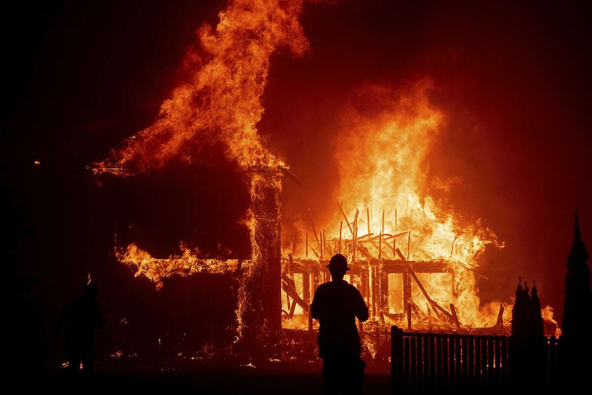 FILE - In this Nov. 8, 2018 file photo, a home burns as a wildfire called Camp Fire rages through Paradise, Calif. Pacific, Gas & Electric Co. initially planned to de-energize local powers lines in vulnerable rural areas during high winds, but has expanded its precautionary power outages to urban areas that could mean multi-day blackouts for cities as larges as San Francisco and San Jose, which could endanger some who depend on electricity for their life support. (AP Photo/Noah Berger, File)
