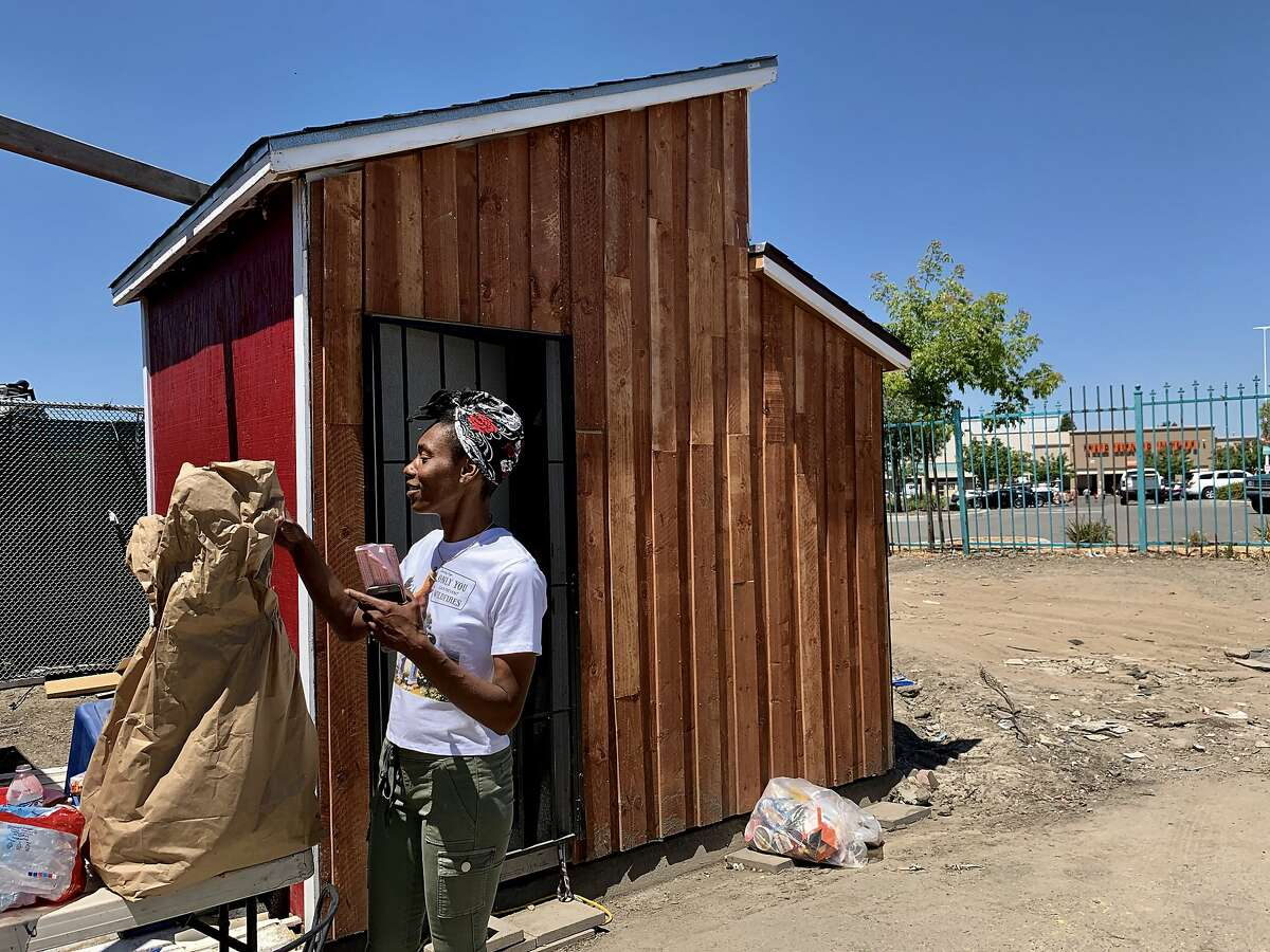 """Markaya Spikes, 38, site leader for the Community of Grace, looks at a bag of donated food outside her tiny house near a Home Depot in Oakland, Calif., on Tuesday, June 4, 2019. Spikes said ways to address homelessness are through the improvement of income and the cost of rent. The Home Depot, located at 4000 Alameda Ave., may pull out of its Oakland store unless the city can curb the crime, tent and RV encampments that have overtaken the area. """"That's the message we got at a meeting with Home Depot representatives,"""" said Oakland City Councilman Noel Gallo, whose district includes the big box hardware store at 4000 Alameda Ave."""