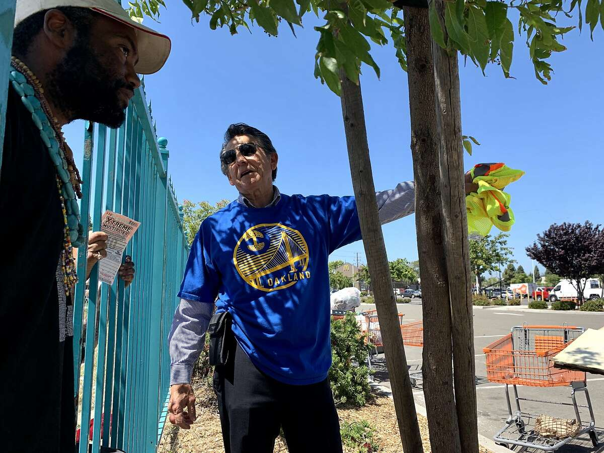 """Oakland City Councilman Noel Gallo (right) speaks to Bryan Heath, 38, a resident of the Community of Grace, located outside of The Home Depot in Oakland, Calif., on Tuesday, June 4, 2019. The Home Depot, located at 4000 Alameda Ave., may pull out of its Oakland store unless the city can curb the crime, tent and RV encampments that have overtaken the area. """"That's the message we got at a meeting with Home Depot representatives,"""" said Oakland City Councilman Noel Gallo, whose district includes the big box hardware store at 4000 Alameda Ave."""
