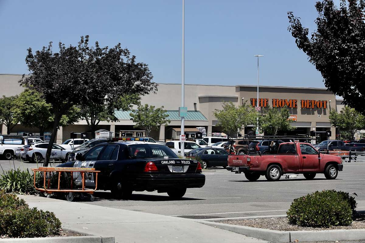 """A Oakland police officer keeps watch over a Home Depot in Oakland, Calif., on Tuesday, June 4, 2019. The Home Depot, located at 4000 Alameda Ave., may pull out of its Oakland store unless the city can curb the crime, tent and RV encampments that have overtaken the area. """"That's the message we got at a meeting with Home Depot representatives,"""" said Oakland City Councilman Noel Gallo, whose district includes the big box hardware store at 4000 Alameda Ave."""