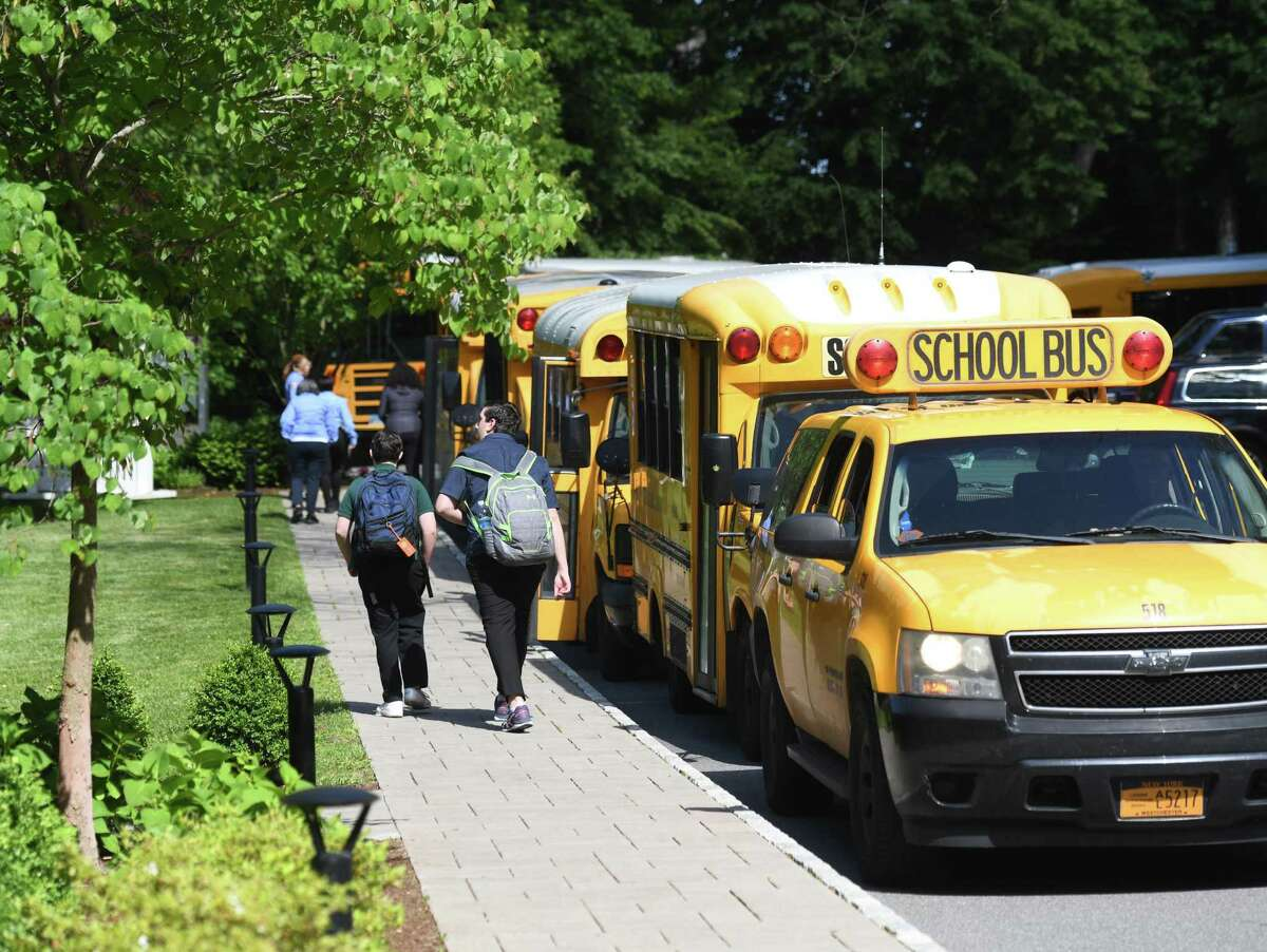 Students board buses during dismissal at Eagle Hill School in Greenwich, Conn. Tuesday, June 4, 2019.