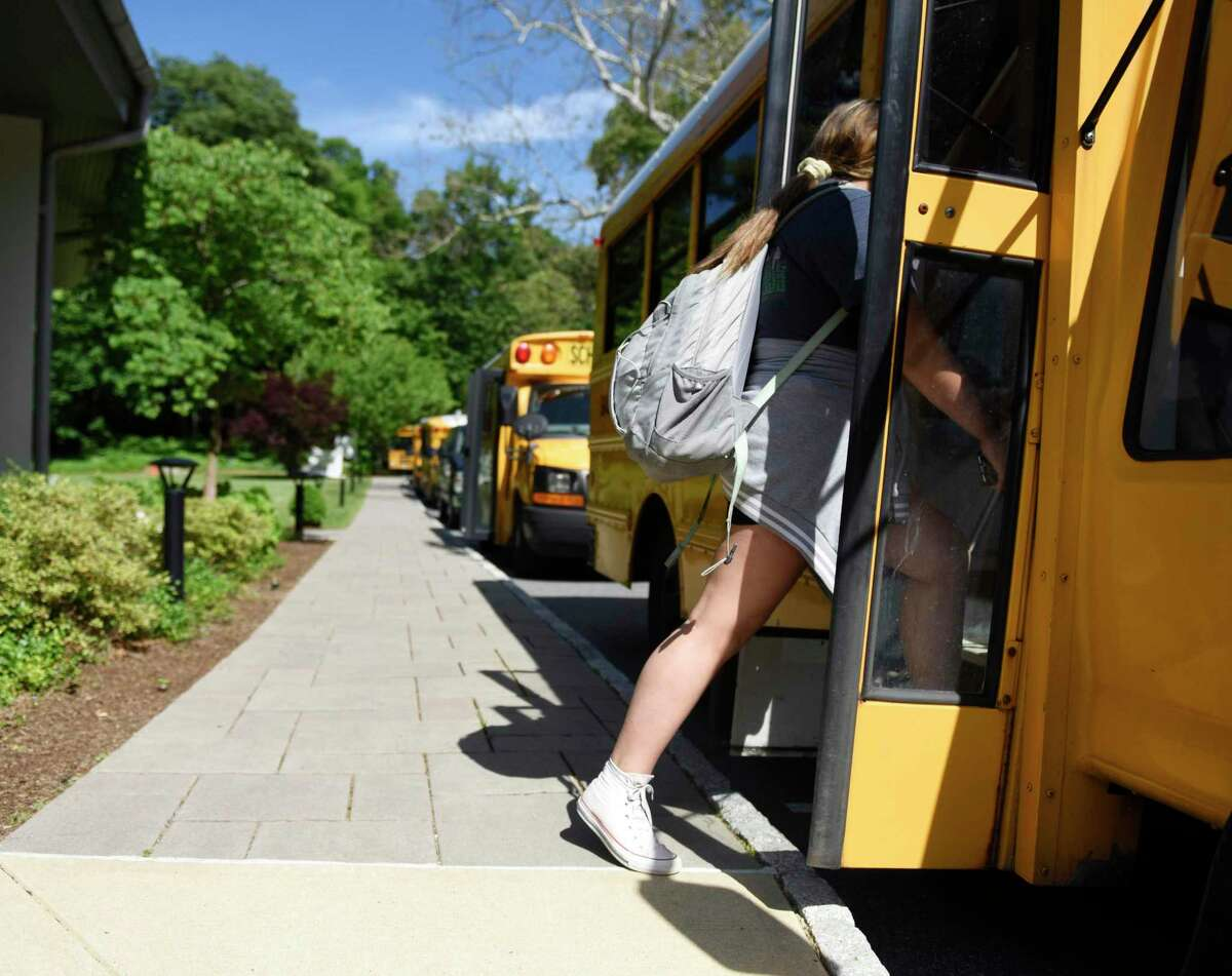 Students board buses during dismissal at Eagle Hill School in Greenwich, Conn. Tuesday, June 4, 2019. Eagle Hill School, an independent school for children with language-based learning differences, will no longer have busing provided by Greenwich Public Schools since the percentage of its attendees who live in Greenwich has dipped below 50 percent and the District is no longer obligated to provide transportation.