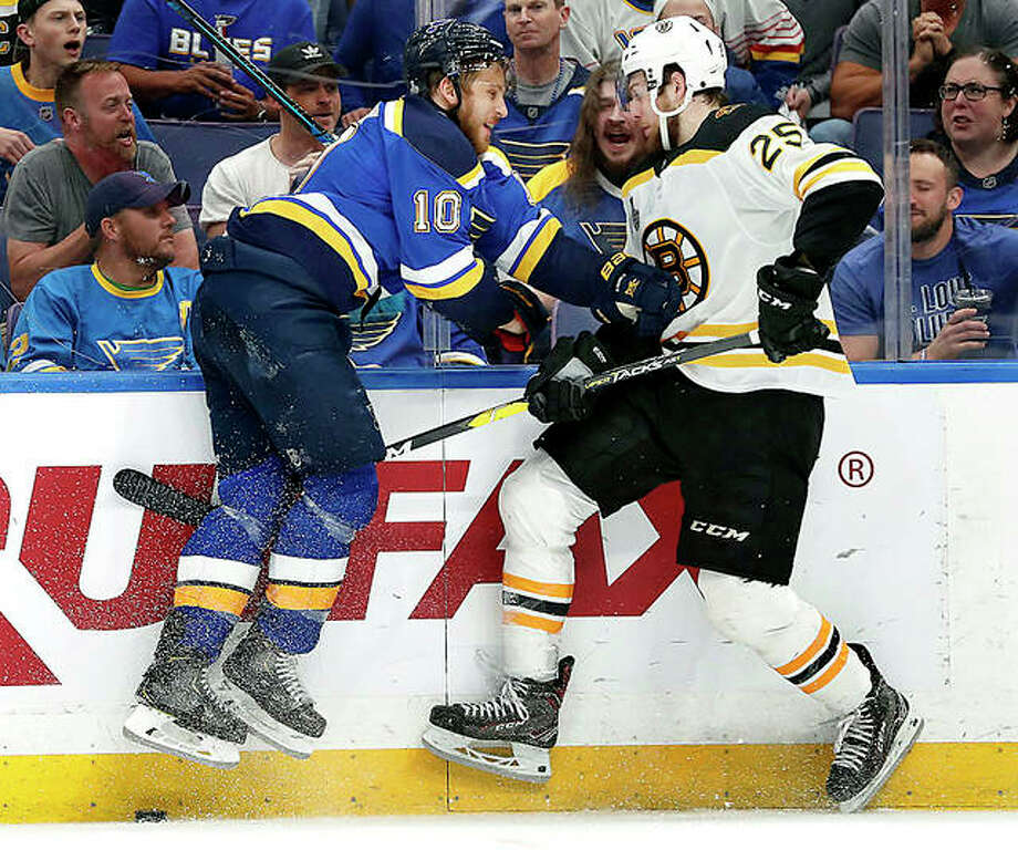 Blues center Brayden Schenn (10) and Boston Bruins defenseman Brandon Carlo leave the ice as they battle for the puck in Monday night's Game 4 of the Stanley Cup Final in St. Louis. The Blues won 4-2 to even the series 2-2. Photo: Jeff Roberson | AP Photo