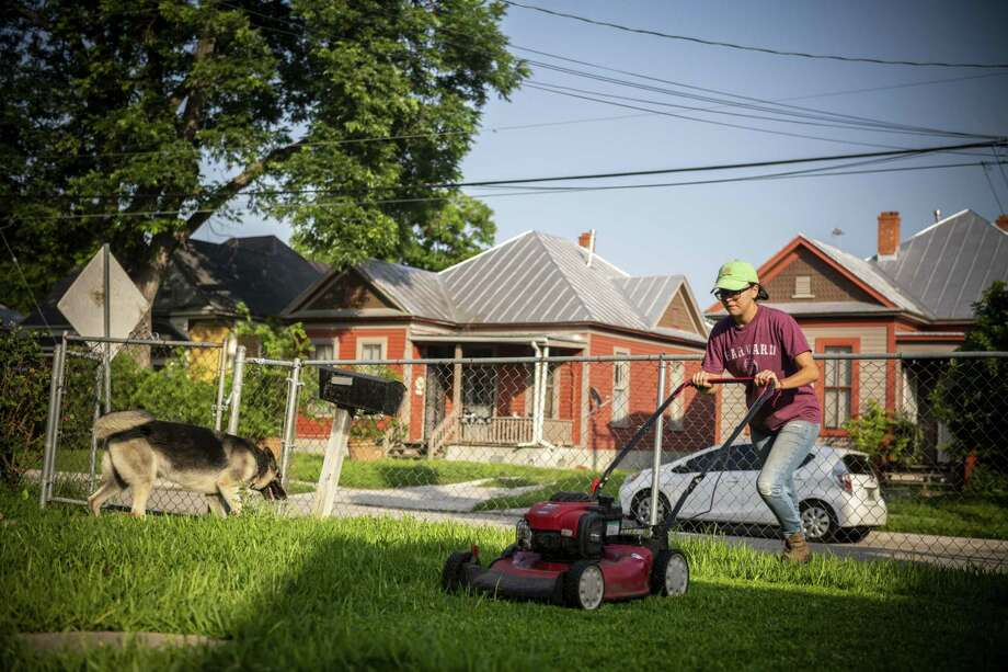 Patricia Prieto cuts the grass as her dog, Yonce, looks for bugs in the freshly cut grass in one of the rentals she manages for an independent investor on West Euclid Avenue in San Antonio. The millennial lives in the back of the property with her boyfriend and their infant son. Photo: Carlos Javier Sanchez / Carlos Javier Sanchez