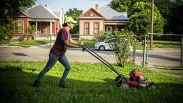 Patricia Prieto cuts the grass at one of the rentals she manages for an independent investor on West Euclid Avenue in San Antonio. The millennial lives in the back of the property with her boyfriend and their infant son.