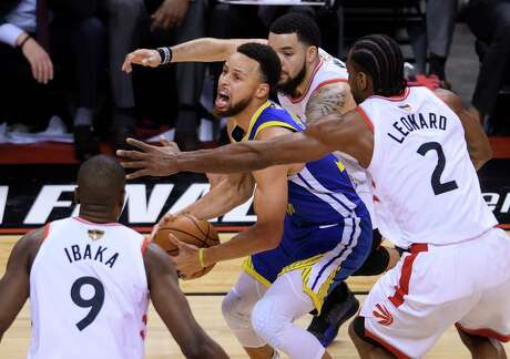 Golden State Warriors guard Stephen Curry, center, is defended by Toronto Raptors forward Kawhi Leonard (2), guard Fred VanVleet, back, and center Serge Ibaka (9) during the second half of Game 2 of basketball's NBA Finals, Sunday, June 2, 2019, in Toronto. (Nathan Denette/The Canadian Press via AP)