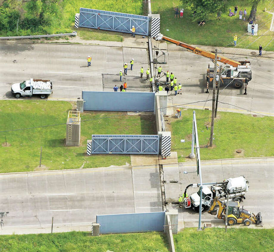 As seen from the air, a small army of workers took to the task Tuesday morning working to close the flood gates on Illinois 3 at the Alton/East Alton line for only the second time in history. Additional photos are on page C-1.
