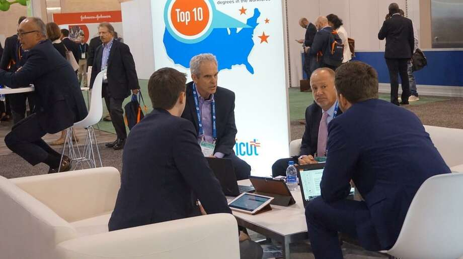 Gary Mathias, chief executive officer and co-founder of Thetis Pharmacceuticals, center left, and Aaron Mathias, director of business development, center right, meet with business associates at Bio 2019 in Philadelphia, Photo: Contributed Photo