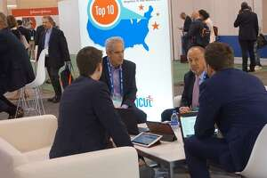 Gary Mathias, chief executive officer and co-founder of Thetis Pharmacceuticals, center left, and Aaron Mathias, director of business development, center right, meet with business associates at Bio 2019 in Philadelphia,