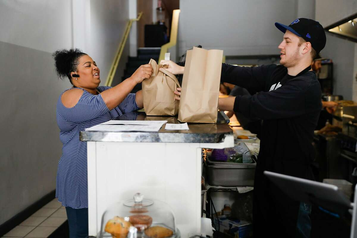 Sylvia Ford (left) grabs her to-go order from Logan Navellier (right) during lunchtime at Delegates restaurant in Oakland, California, on Tuesday, June 4, 2019.