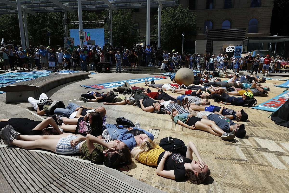 Supporters spell out a message with their bodies at a rally Tuesday, June 4, 2019 for a group of young people who filed a lawsuit saying U.S. energy policies are causing climate change and hurting their future. The group faces a major hurdle Tuesday as lawyers for the Trump administration argue to stop the case from moving forward. in Portland, Ore. (AP Photo/Steve Dipaola)