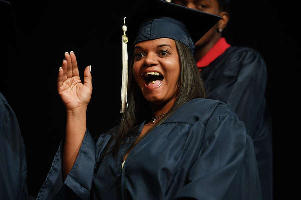 Graduate Sandra Lopez waves to family as she crosses the stage during the Bridgeport Adult Education Graduation at the Klein Memorial Auditorium in Bridgeport, Conn. on Tuesday, June 3, 2019.