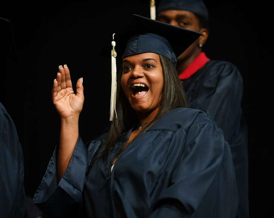Graduate Sandra Lopez waves to family as she crosses the stage during the Bridgeport Adult Education Graduation at the Klein Memorial Auditorium in Bridgeport, Conn. on Tuesday, June 3, 2019. Photo: Brian A. Pounds / Hearst Connecticut Media / Connecticut Post