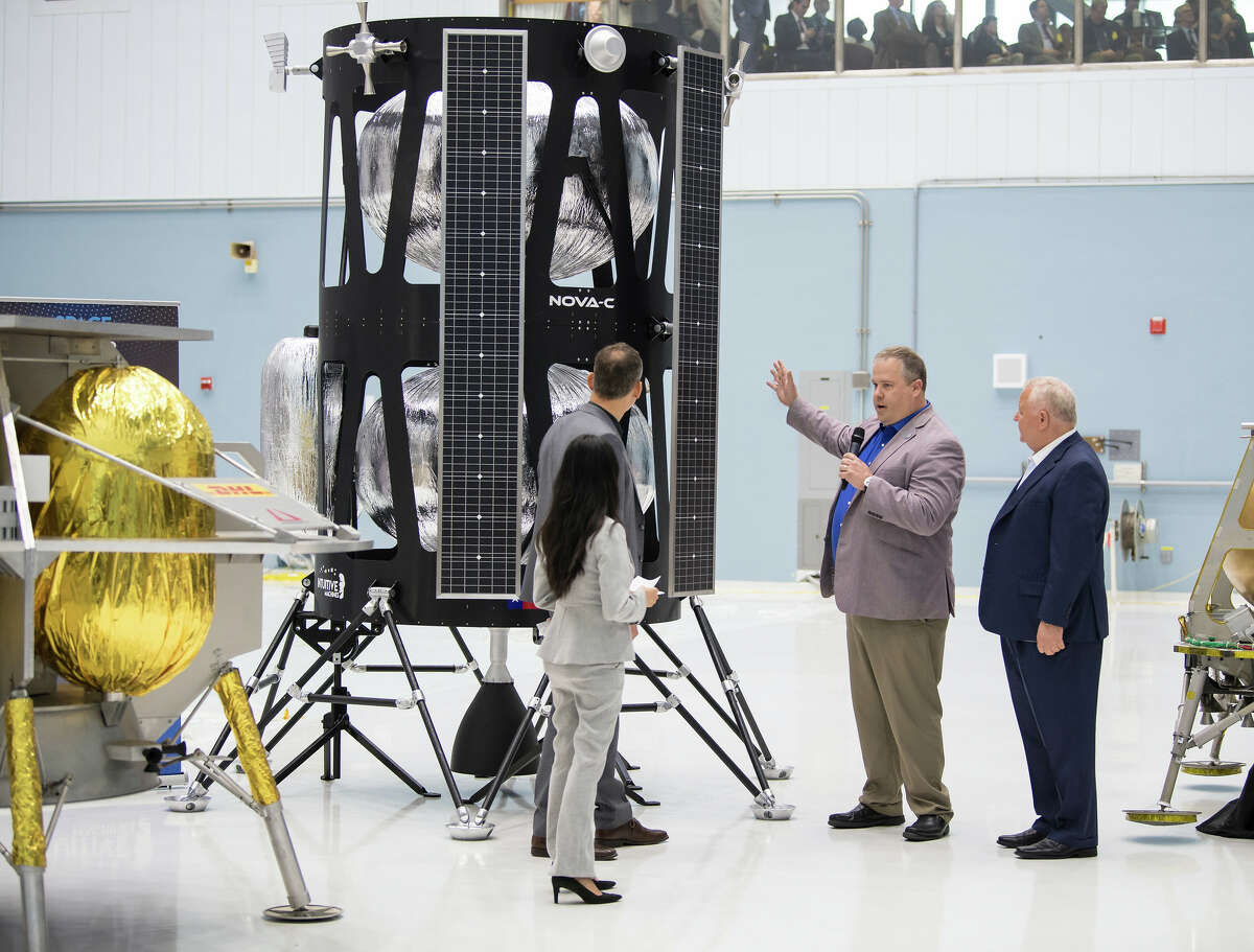 Vice president of Research and Development for Intuitive Machines, Tim Crain, second from right, speaks with Thomas Zurbuchen, NASA Associate Administrator for the Science Mission Directorate, second from left, about the company's lunar lander, Friday, May 31, 2019, at Goddard Space Flight Center in Maryland. Intuitive Machines was one of three companies selected to provide the first lunar landers for the Artemis program's lunar surface exploration.
