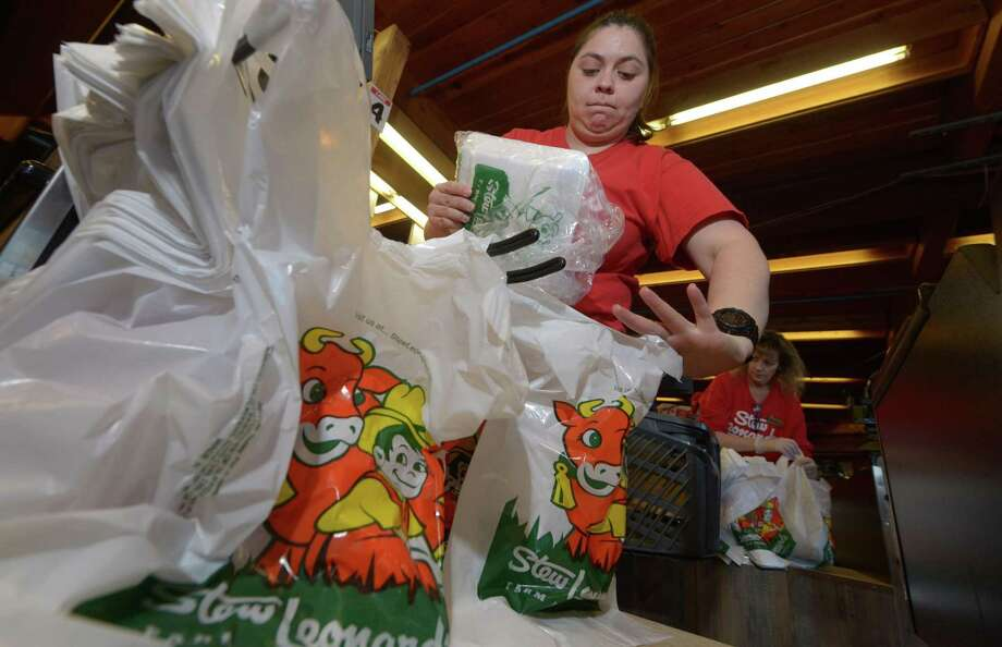 Cashier Caren Montero bags groceries with the Stew Leonard's iconic plastic bags at the store in Norwalk. Photo: Erik Trautmann / Hearst Connecticut Media / Norwalk Hour