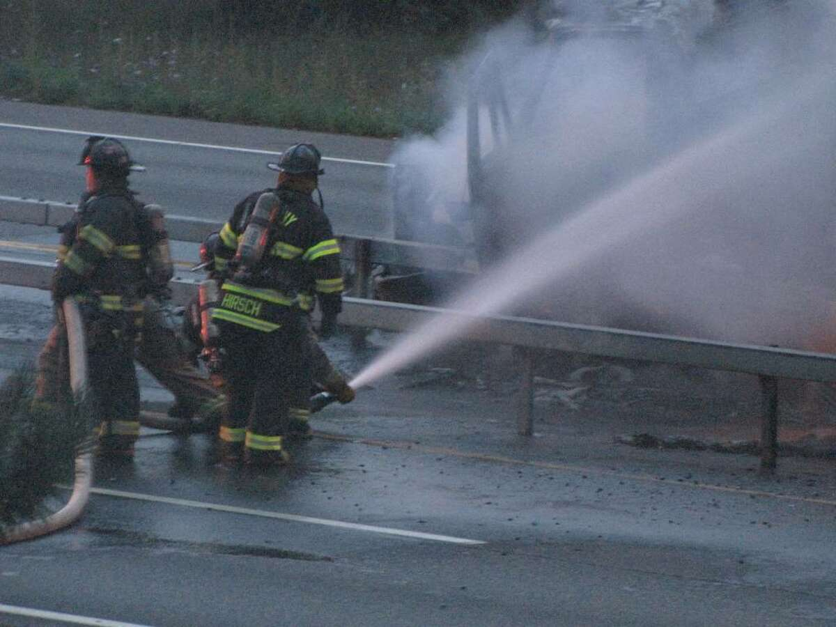 Firefighters pour water on a tractor-trailer filled with paper products that caught fire on Interstate 787 after an early morning collision. (Special to the Times Union)